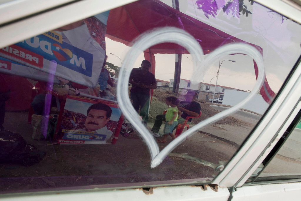 . In this April 8, 2013 photo, supporters of the ruling party presidential candidate and acting President Nicolas Maduro are reflected in a car window in Valencia, Venezuela. Outside Venezuela\'s capital, power outages, food shortages and unfinished projects abound; important factors heading into Sunday\'s election to replace Chavez, who died last month after a long battle with cancer. Maduro, is favored to win, largely on the strength of Chavez\'s generous anti-poverty programs. But recent polls show that support for Maduro, Chavez\'s hand-picked successor, may be eroding. (AP Photo/Ramon Espinosa)