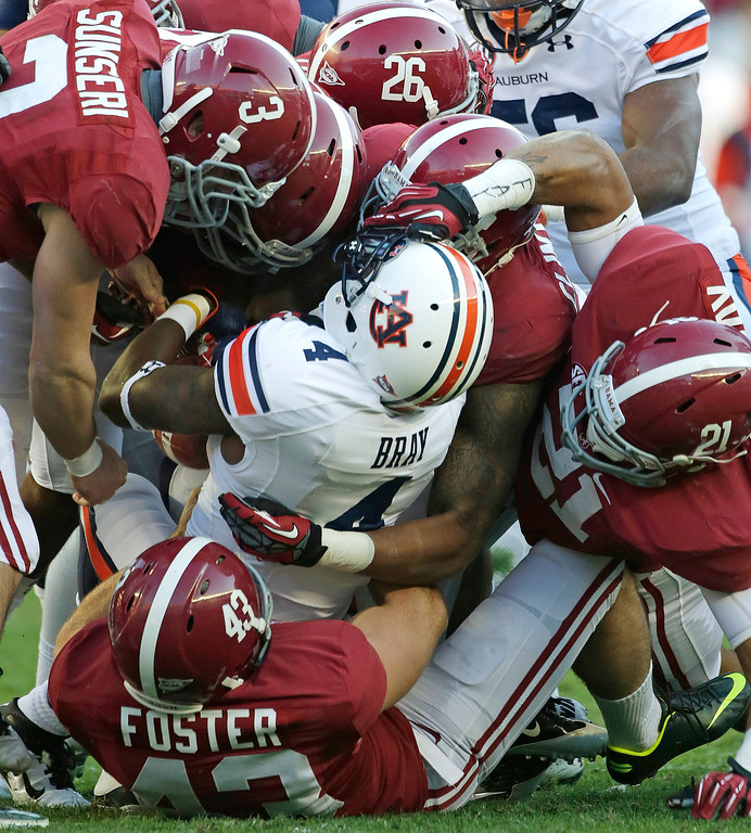 . Auburn wide receiver Quan Bray (4) is stopped by a host of Alabama players during the first half of a NCAA college football game at Bryant-Denny Stadium in Tuscaloosa, Ala., Saturday, Nov. 24, 2012. Visibile for Alabama is kicker Cade Foster (43), defensive back Vinnie Sunseri (3), defensive back Landon Collins (26) defensive back Brent Calloway (21). (AP Photo/Dave Martin)