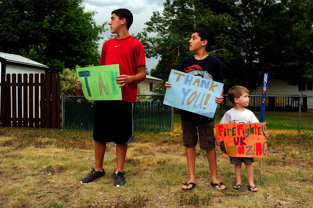 . From left, Bailey, 13, Riley, 10, and Brody, 3, Makloski hold signs for returning firefighters as the High Park Fire continues to burn in the mountains west of Fort Collins on Tuesday, June 26, 2012. AAron Ontiveroz, The Denver Post