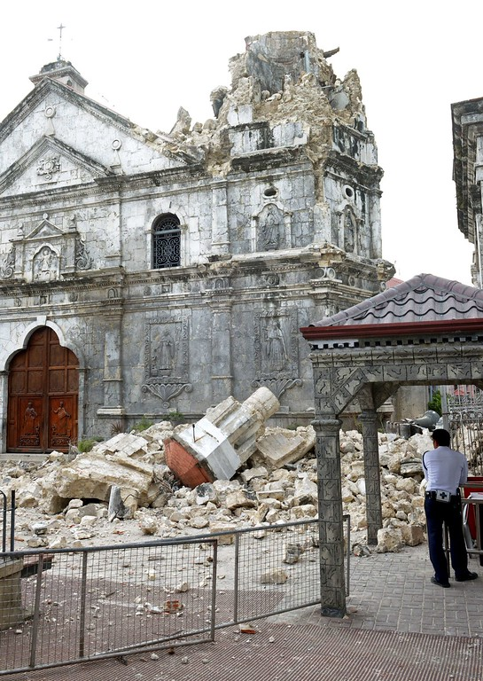 . A guard stands beside the ruins of Basilica Minore del Santo Nino bell tower following a 7.1-magnitude quake in Cebu on October 15, 2013.    AFP PHOTO / Jay  DIRECTO/AFP/Getty Images