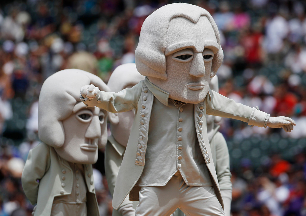 . As part of a tourism promotion to visit Mount Rushmore in the Black Hills of South Dakota, a likeness of the nation\'s first president, George Washington, throws out the ceremonial first pitch before the Philadelphia Phillies face the Colorado Rockies in  a baseball game in Denver, Saturday, June 15, 2013. (AP Photo/David Zalubowski)