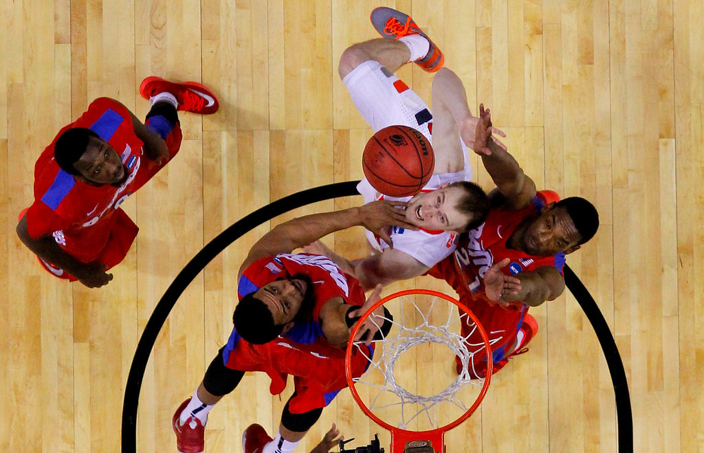. Syracuse\'s Trevor Cooney (10) shoots between Dayton\'s Devon Scott, second from left, and Dyshawn Pierre, right, as Khari Price, left, watches during the first half of a third-round game in the NCAA men\'s college basketball tournament in Buffalo, N.Y., Saturday, March 22, 2014. (AP Photo/Bill Wippert)