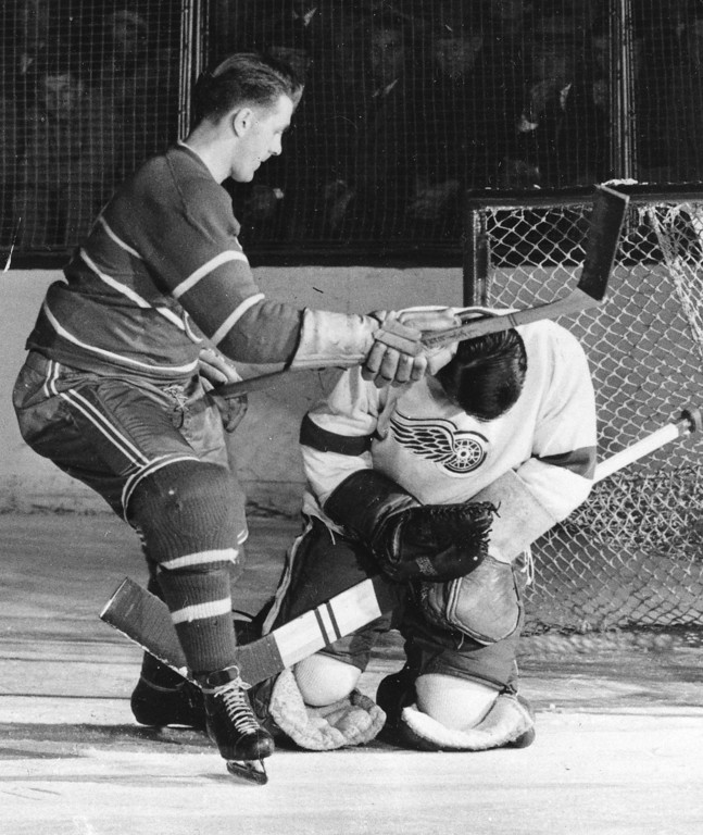 ". Detroit Red Wings goalie Terry Sawchuk takes a blow to the head from the stick of Montreal Canadiens Maurice ""Rocket\"" Richard during game action in Detroit, Oct. 22, 1950.  (AP Photo/Preston Stroup)"