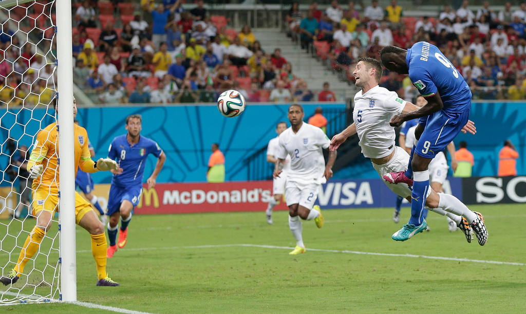. Italy\'s Mario Balotelli (9) heads the ball past England\'s Gary Cahill (5) and goalkeeper Joe Hart, left, to score Italy\'s second goal during the group D World Cup soccer match between England and Italy at the Arena da Amazonia in Manaus, Brazil, Saturday, June 14, 2014. (AP Photo/Marcio Jose Sanchez)