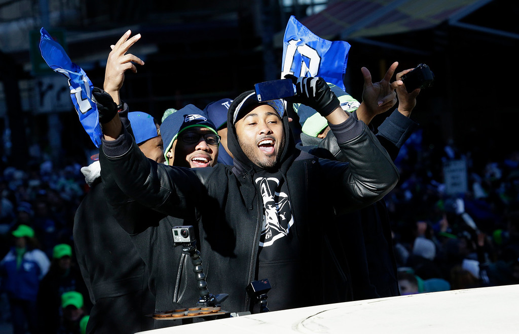 . Seattle Seahawks linebacker and Super Bowl MVP Malcolm Smith gestures to fans during the Super Bowl champions parade, Wednesday, Feb. 5, 2014, in Seattle. (AP Photo/Ted S. Warren)