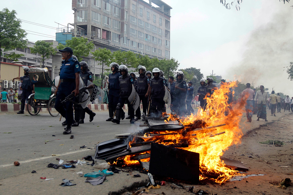 . Bangladeshi policemen walk past furniture set on fire by garment workers during a protest against the collapse of an eight-story building that housed several garment factories and poor working conditions of the employees, in Dhaka, Bangladesh, Saturday, April 27, 2013. Police in Bangladesh took into custody five people in connection with the collapse of a shoddily-constructed building that collapsed this week, as rescue workers pulled out 19 survivors out of the rubble on Saturday and vowed to continue as long as necessary to find others despite fading hopes. (AP Photo/A.M. Ahad)
