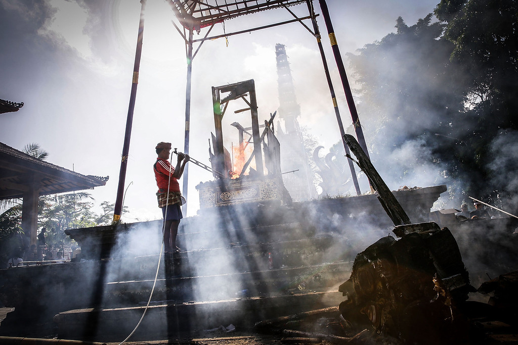 . A Balinese man controls the burning sarcophagus at the cemetery during the Royal cremation ceremony on November 1, 2013 in Ubud, Bali, Indonesia.  (Photo by Agung Parameswara/Getty Images)