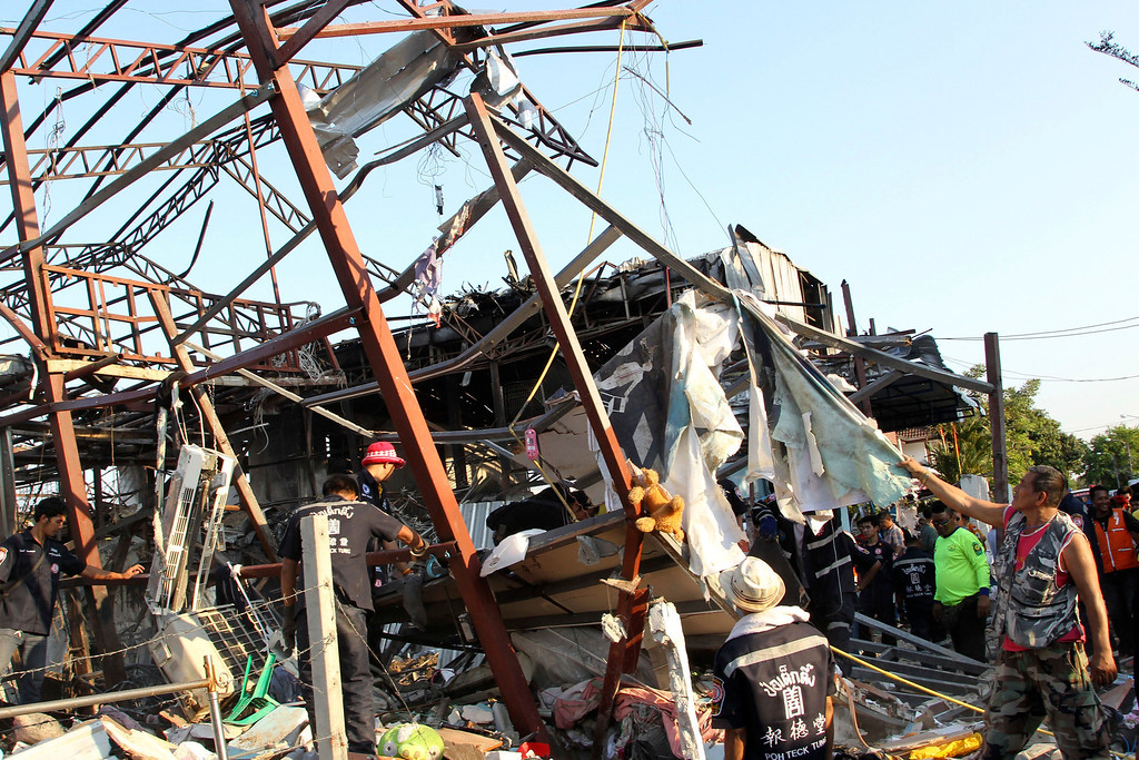 . Thai charity workers sift through the wreckage of a building after a bomb explosion at a scrap shop in Bangkok, Thailand Wednesday, April 2, 2014. (AP Photo/Apichart Weerawong)