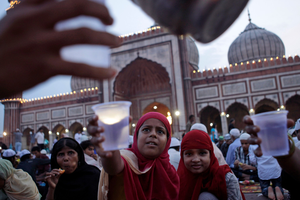 . Muslim girls stretch their hands out to receive water after breaking fast at Jama Masjid ahead of Eid al-Fitr in New Delhi, India,Thursday, Aug 8, 2013. Eid al-Fitr marks the end of the holy month of Ramadan, during which Muslims all over the world fast from sunrise to sunset. (AP Photo/Tsering Topgyal)