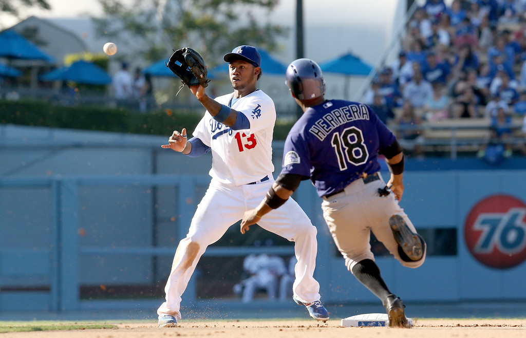 . LOS ANGELES, CA - JULY 13: Shortstop Hanley Ramirez #13 of the Los Angeles Dodgers takes the throw before tagging out Jonathan Herrera #18 of the Colorado Rockies on a stolen base attempt in the sixth inning at Dodger Stadium on July 13, 2013 in Los Angeles, California.  (Photo by Stephen Dunn/Getty Images)