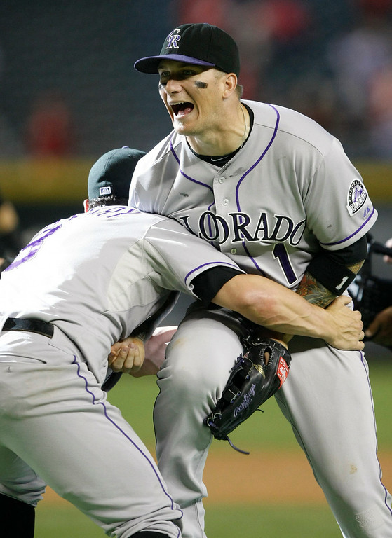 . Colorado Rockies right fielder Brandon Barnes (1) and Michael McKenry (8) celebrate after defeating the Arizona Diamondbacks 5-3 in 10 innings of a baseball game, Sunday, Aug. 10, 2014, in Phoenix. (AP Photo/Rick Scuteri)