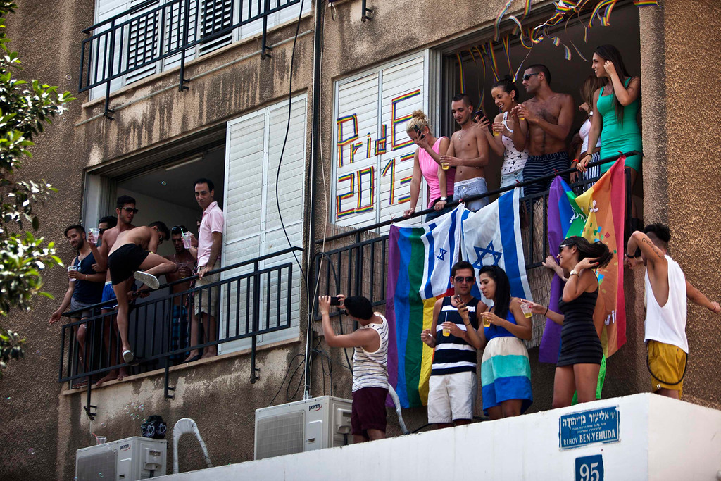 . People take part at the annual Gay Pride parade from balconies in Tel Aviv June 7, 2013. REUTERS/Nir Elias
