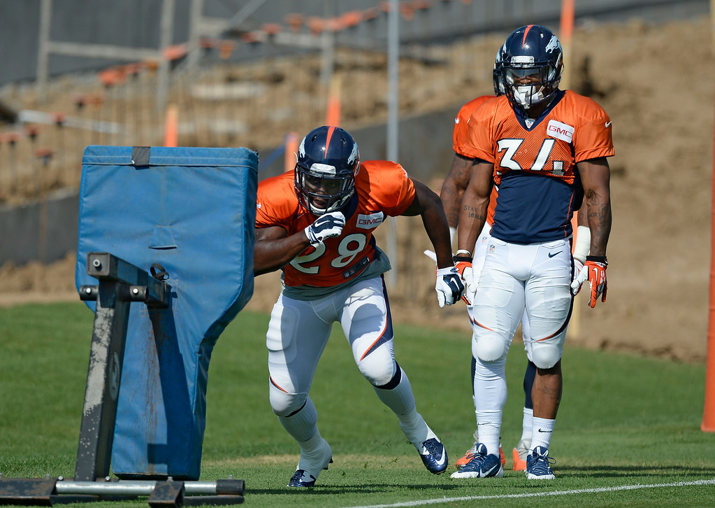 . Denver Broncos running back Montee Ball (28) hits the sled during drills on day five of the Denver Broncos 2014 training camp July 28, 2014 at Dove Valley. (Photo by John Leyba/The Denver Post)