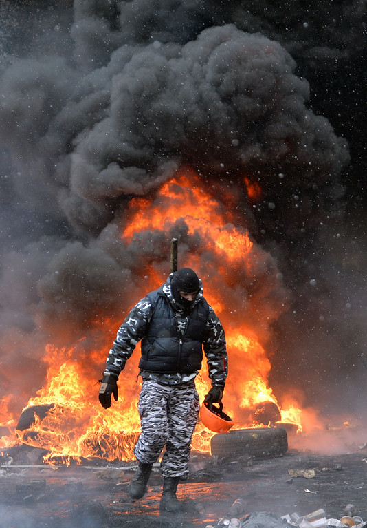 . A demonstrator walks near burning tyres during clashes between protestors and police in the center of Kiev on January 22, 2014.  AFP PHOTO / SERGEI SUPINSKY/AFP/Getty Images