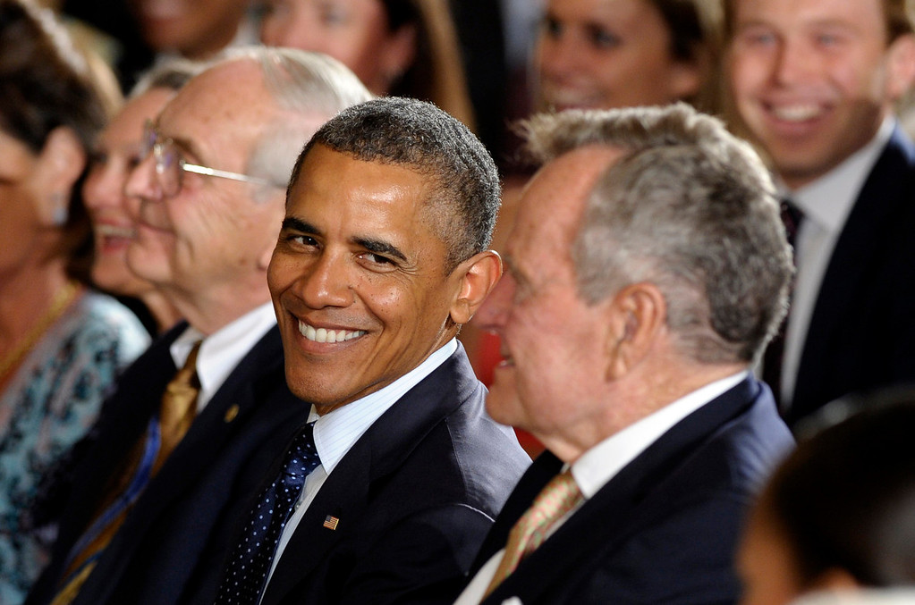 """. President Barack Obama, center, looks at former President George H. W. Bush, right, during a ceremony to recognizes the 5,000th Daily Point of Light Award in the East Room of the White House in Washington, Monday, July 15, 2013. Obama welcomed Bush to the White House in a salute to public service and to the drive for volunteerism that the 41st president inspired with his \""""thousand points of light\"""" initiative more than two decades ago.  (AP Photo/Susan Walsh)"""