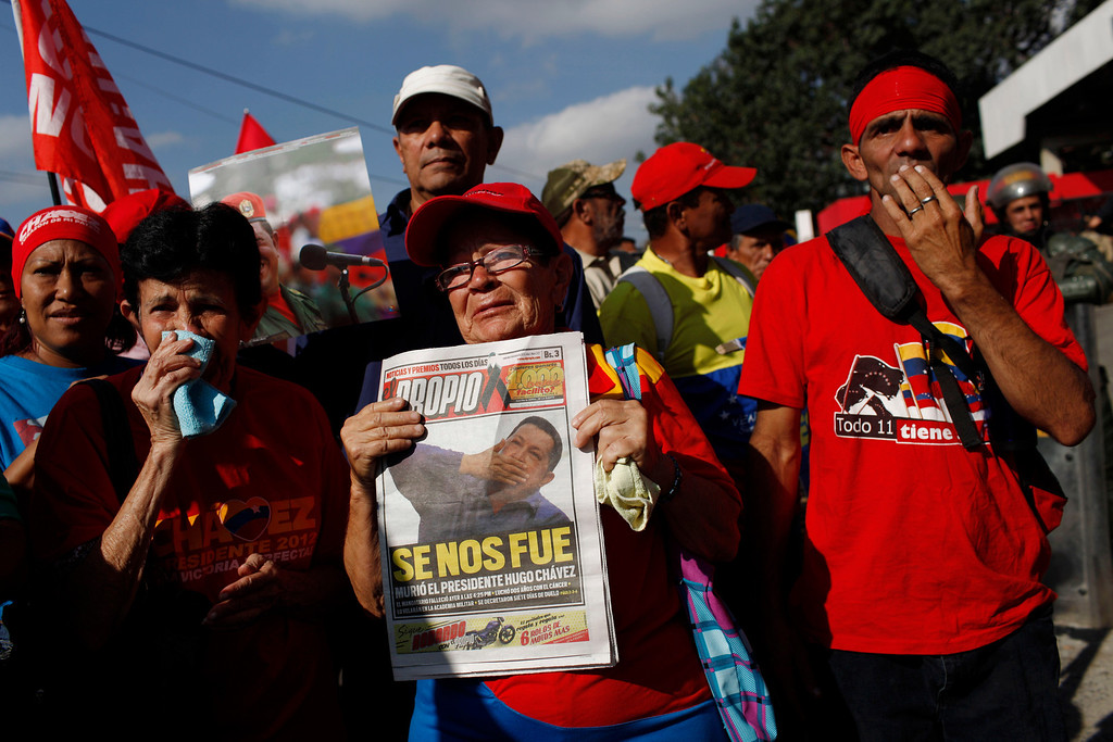 """. A woman holds a newspaper with the headline in Spanish \""""He\'s left us\"""" as she stands with fellow supporters of Venezuela\'s late President Hugo Chavez to watch his coffin pass by, as it is paraded from the hospital where he died on Tuesday to a military academy where it will remain until his funeral in Caracas, Venezuela, Wednesday, March 6, 2013. . (AP Photo/Rodrigo Abd)"""