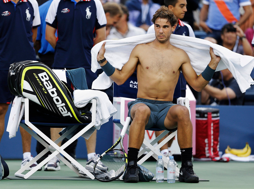 . Rafael Nadal, of Spain, wipes sweat from his back during a break between games against Novak Djokovic, of Serbia, during the men\'s singles final of the 2013 U.S. Open tennis tournament, Monday, Sept. 9, 2013, in New York. (AP Photo/Darron Cummings)