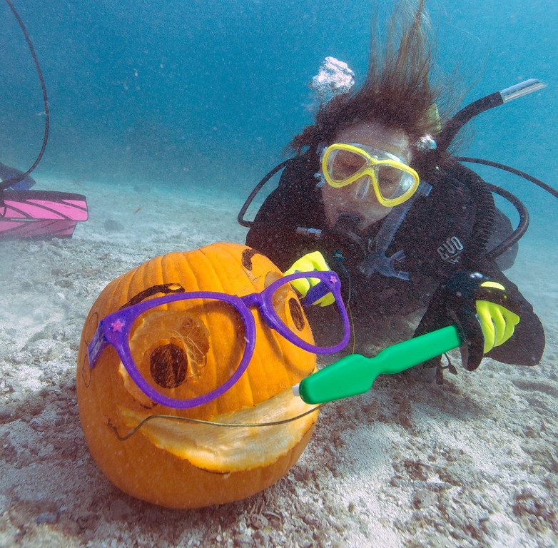 . In this Saturday, Oct. 19, 2013, photo provided by the Florida Keys News Bureau, Jana Vandelaar uses an oversize toothbrush on a jack-o-lantern she sculpted underwater at the Underwater Pumpkin Carving Contest in the Florida Keys National Marine Sanctuary off Key Largo, Fla. Vandelaar, who won top honors, was one of 30 contestants who competed in the offbeat event organized by the Amoray Dive Resort. (AP Photo/Florida Keys News Bureau, Bob Care)