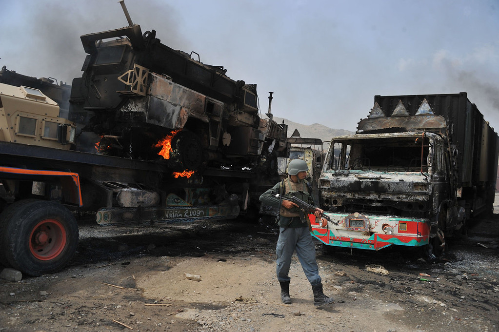 . Afghan security official stand guard near burning military vehicles after a clash between Taliban and Afghan security forces in Torkham on September 2, 2013. A group of Taliban suicide bombers and gunmen have attacked a US base near the Pakistani border in eastern Afghanistan, sparking a three-hour shootout, officials said. No member of the US-led NATO mission in Afghanistan was killed in the attack on a base in Nangarhar province, said a spokesman for the International Security Assistance Force (ISAF).   Noorullah Shirzada/AFP/Getty Images