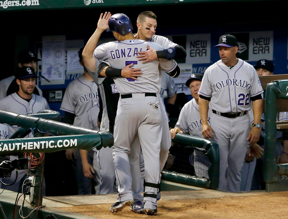 . Colorado Rockies\' Carlos Gonzalez (5) is greeted at the top steps of the dugout by Troy Tulowitzki as manager Walt Weiss (22) stands near following Gonzalez\' solo home run off of Texas Rangers starting pitcher Colby Lewis in the fourth inning of a baseball game, Wednesday, May 7, 2014, in Arlington, Texas. (AP Photo/Tony Gutierrez)