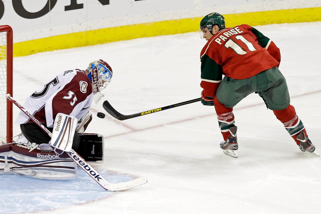 . Colorado Avalanche goalie Jean-Sebastien Giguere, left, stops a shootout goal-attempt by Minnesota Wild\'s Zach Parise duringf an NHL hockey game on Thursday, Feb. 14, 2013, in St. Paul, Minn. The Avalanche won 4-3. (AP Photo/Jim Mone)