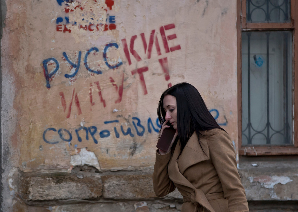 ". In this Friday, March 7, 2014 file photo, a woman passes by a graffiti that reads ""The Russians are coming - Resistance\"" in Simferopol, Ukraine. For the ethnic Ukrainians and Tatars who are the minority in the strategic peninsula, it is fear that dominates days before Crimea votes in a referendum on joining Russia. (AP Photo/Vadim Ghirda, File)"