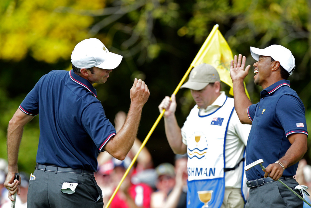 . United States\' Matt Kuchar, left, and teammate Tiger Woods celebrate Kuchar\'s birdie on the first hole during a four-ball match against the International team at the Presidents Cup golf tournament at Muirfield Village Golf Club Thursday, Oct. 3, 2013, in Dublin, Ohio. (AP Photo/Jay LaPrete)