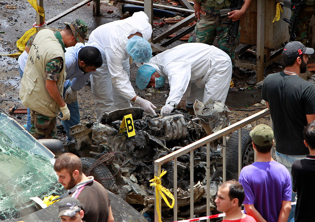 . Forensic experts inspect the remnants of a car bomb at the scene of a bombing in the Beir el-Abed, a southern suburb of Beirut, Lebanon, Tuesday, July 9, 2013.  (AP Photo/Bilal Hussein)