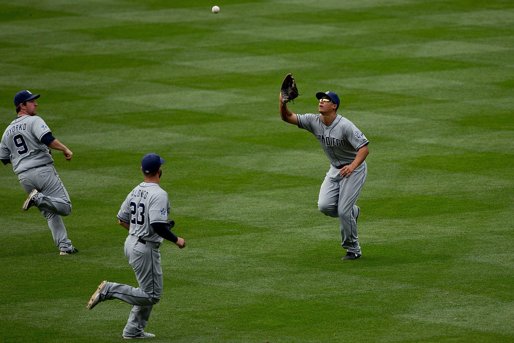 . Will Venable #25 of the San Diego Padres makes a catch on the run after calling off Jedd Gyorko #9 and Yonder Alonso #23 for the first out of the ninth inning against the Colorado Rockies at Coors Field on May 18, 2014 in Denver, Colorado. The Rockies defeated the Padres 8-6 in 10 innings. (Photo by Justin Edmonds/Getty Images)