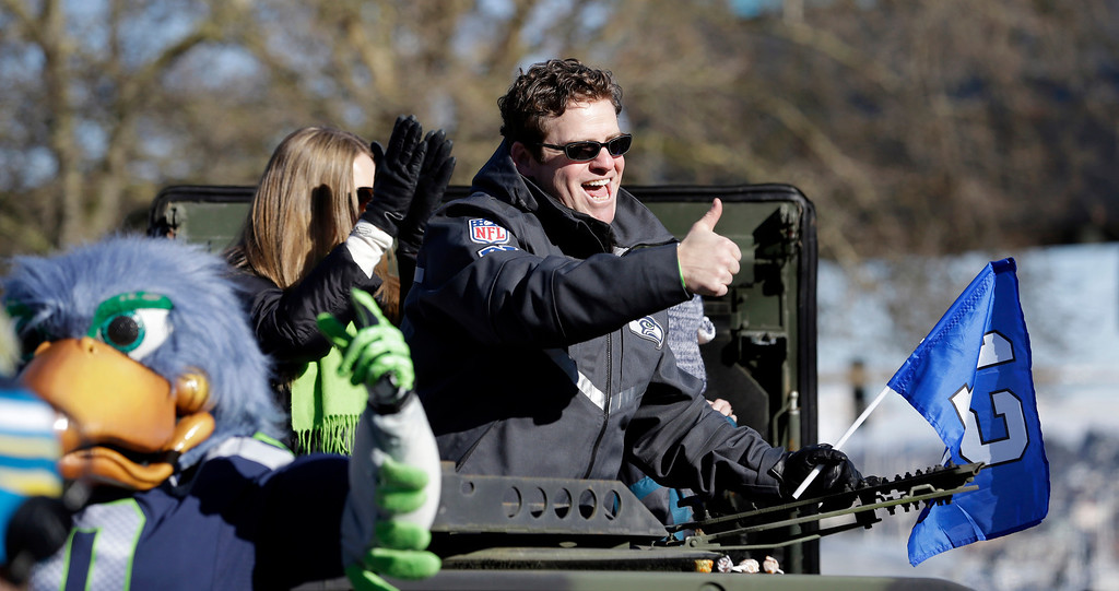 . Seattle Seahawks general manager John Schneider gives a thumbs-up to fans at a parade for the NFL football Super Bowl champions Wednesday, Feb. 5, 2014, in Seattle.  (AP Photo/Elaine Thompson)