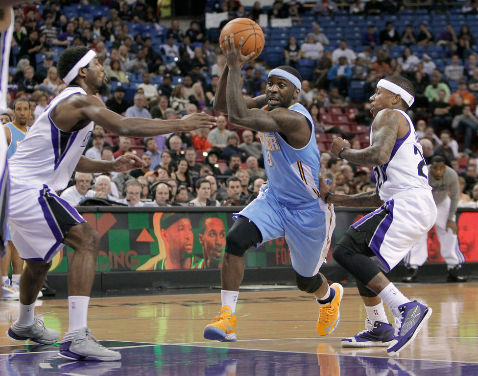 . Denver Nuggets guard Ty Lawson drives between Sacramento Kings\' John Salmons, left, and Isaiah Thomas during the first quarter of an NBA basketball game in Sacramento, Calif., Tuesday, March 5, 2013. (AP Photo/Rich Pedroncelli)