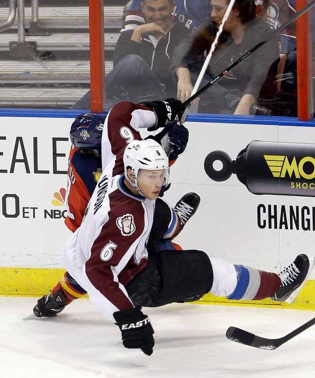 . Colorado Avalanche defenseman Erik Johnson (6) goes down after checking Florida Panthers center Jonathan Huberdeau (11) during the second period of an NHL hockey game in Sunrise, Fla., Friday, Jan. 24, 2014. (AP Photo/Alan Diaz)