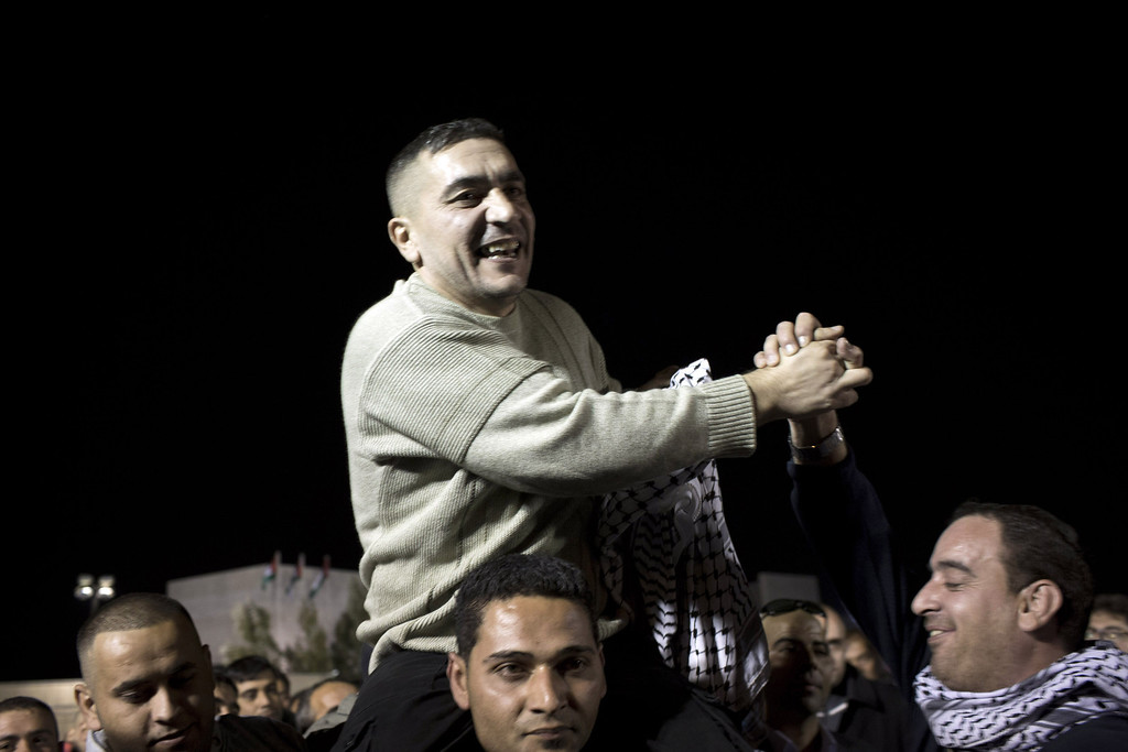 . A released Palestinian prisoner is greeted by family members and friends as he arrives with other freed prisoners to the Mukata Presidential Compound in the early morning hours on October 30, 2013 in Ramallah, West Bank. The 26 Palestinian prisoners were released by Israel as part of the terms of renewed U.S.-brokered peace talks. (Photo by Oren Ziv/Getty Images)