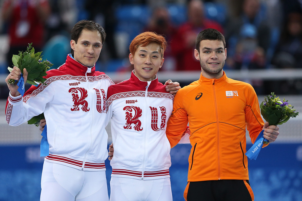. SOCHI, RUSSIA - FEBRUARY 15:  Gold medallist Victor An (C) of Russia stands on the podium during the flower ceremony with silver medallist Vladimir Grigorev (L) of Russia and bronze medallist Sjinkie Knegt of Netherlands after the Men\'s 1000 m Final Short Track Speed Skating on day 8 of the Sochi 2014 Winter Olympics at the Iceberg Skating Palace on February 15, 2014 in Sochi, Russia.  (Photo by Matthew Stockman/Getty Images)