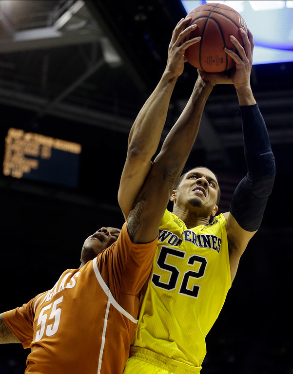 . Michigan forward Jordan Morgan (52) battles for a rebound against Texas center Cameron Ridley (55) during the first half of a third-round game of the NCAA college basketball tournament Saturday, March 22, 2014, in Milwaukee. (AP Photo/Morry Gash)