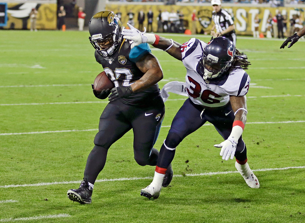 . Jacksonville Jaguars running back Maurice Jones-Drew, left, gains yardage before he is run out of bounds by Houston Texans strong safety D.J. Swearinger (36) during the first half of an NFL football game in Jacksonville, Fla., Thursday, Dec. 5, 2013.(AP Photo/John Raoux)
