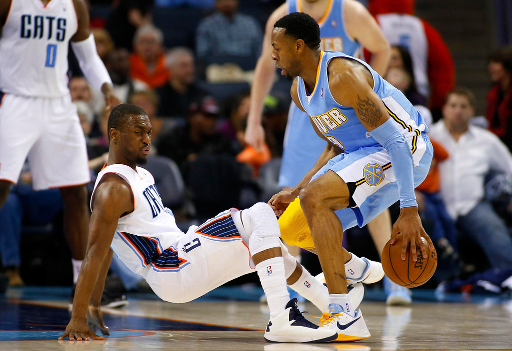 . Charlotte Bobcats point guard Kemba Walker (L) falls to the ground as he takes a charge against Denver Nuggets shooting guard Andre Iguodala (R) during the second half of their NBA basketball game in Charlotte, North Carolina February 23, 2013. REUTERS/Chris Keane