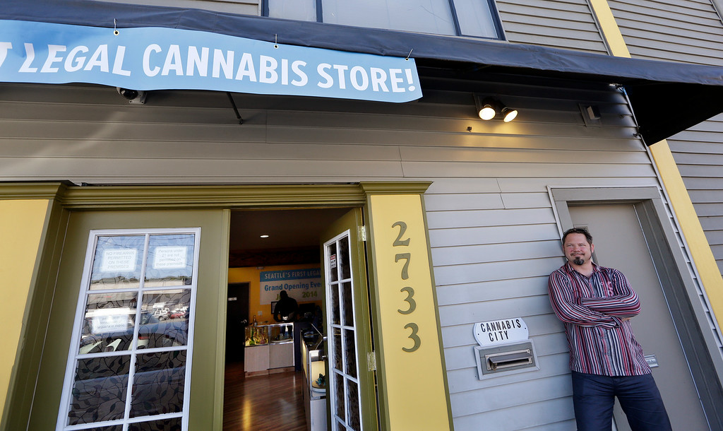 . Cannabis City owner James Lathrop briefly leans against the exterior of his new recreational marijuana store Monday, July 7, 2014, in Seattle. The shop will be the first and, initially, only store in Seattle to legally sell recreational pot when sales begin Tuesday. (AP Photo/Elaine Thompson)