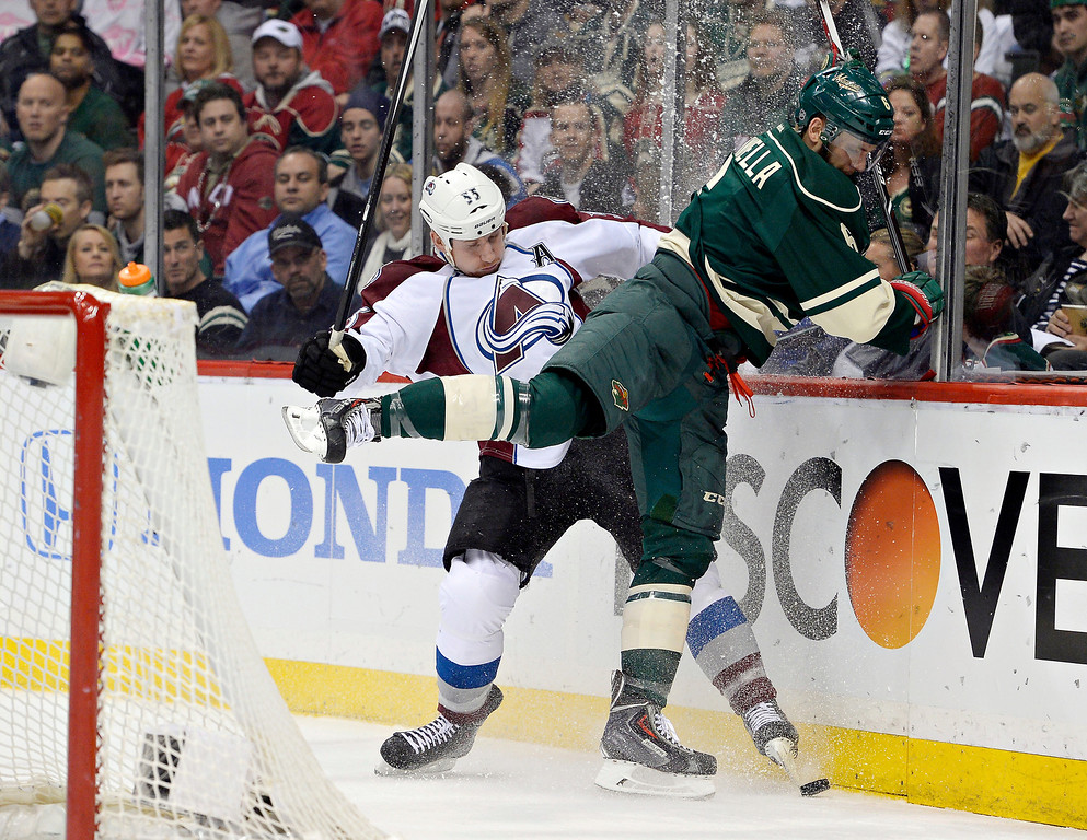 . Colorado Avalanche left wing Cody McLeod (55) and Minnesota Wild defenseman Marco Scandella (6) crash the boards hard going after the puck in the first period April 24, 2014 at Xcel Energy Center. (Photo by John Leyba/The Denver Post)
