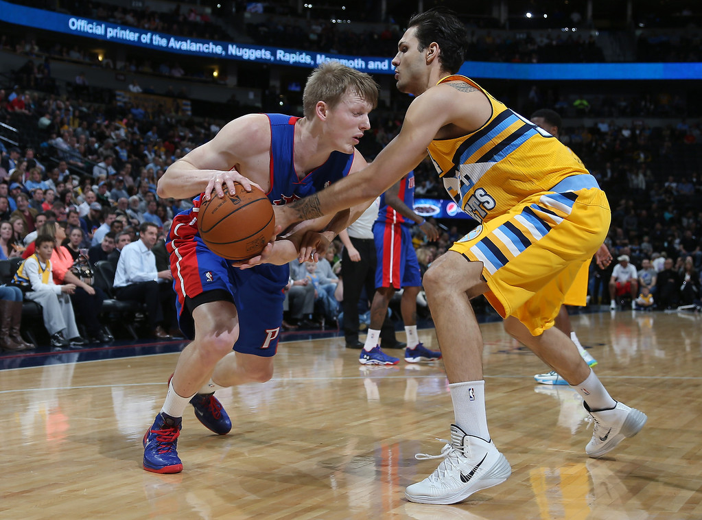. Detroit Pistons forward Kyle Singler, left, works the ball inside for a shot as Denver Nuggets guard Evan Fournier, of France, covers in the first quarter of an NBA basketball game in Denver on Wednesday, March 19, 2014. (AP Photo/David Zalubowski)