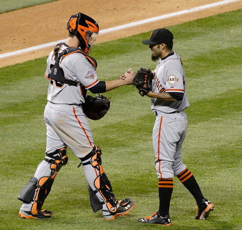 . Sergio Romo (54) of the San Francisco Giants shakes hands with Buster Posey; (28) after striking out Dexter Fowler (24) of the Colorado Rockies for the last out in the ninth inning May 16, 2013 at Coors Field. The Giants defeated the Rockies 8-6. (Photo By John Leyba/The Denver Post)