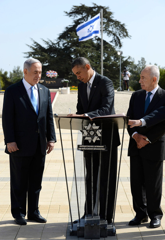 . In this handout photograph supplied by the Government Press Office of Israel (GPO), U.S. President Barack Obama writes a message in the Yad Vashem visitor book next to Israel\'s Prime Minister Benjamin Netanyahu and President Shimon Peres during a visit to Yad Vashem at Mount Herzl on March 22, 2013 in Jerusalem, Israel. (Photo by Kobi Gideon/GPO via Getty Images)