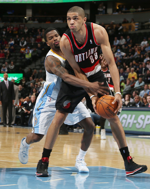 . Portland Trail Blazers forward Nicolas Batum, front, of France, is fouled after picking up a loose ball by Denver Nuggets guard Aaron Brooks in the fourth quarter of an NBA basketball game in Denver, Tuesday, Feb. 25, 2014. Portland won 100-95. (AP Photo/David Zalubowski)