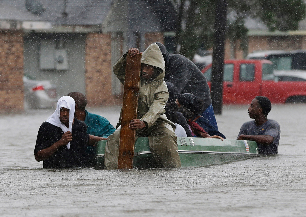 . In this Aug. 30, 2012 file photo, residents evacuate their flooded neighborhood in LaPlace, La. Hurricane Isaac staggered toward central Louisiana, its weakening winds driving storm surge into portions of the coast and the River Parishes between New Orleans and Baton Rouge. (AP Photo/Eric Gay, File)