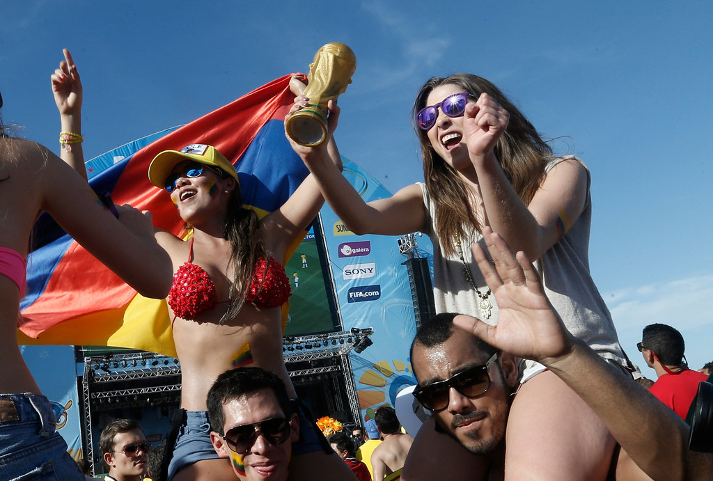 . Colombia soccer fans celebrate during the game against Greece inside the FIFA Fan Fest area on Copacabana beach, Rio de Janeiro, Brazil, Saturday, June 14, 2014. Colombia defeated Greece 3-0. (AP Photo/Silvia Izquierdo)