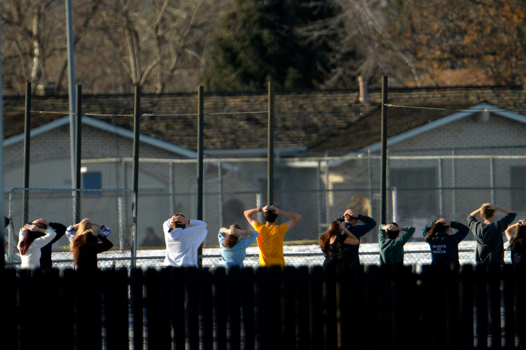 . CENTENNIAL, CO. - December 13: Students with hands behind their heads in line to be searched before joining others waiting to be bussed to their release points from the high school sports area after a student carried a shotgun into Arapahoe High School and opened fire on Friday, wounding two fellow students before apparently killing himself December 13, 2013 Centennial, CO. (Photo By Joe Amon/The Denver Post)