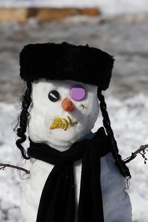. A snowman with a hat traditionally worn by ultra-Orthodox Jews is seen in a snow-covered park in Jerusalem January 10, 2013. The worst snowstorm in 20 years shut government offices, public transport and schools in Jerusalem and along the northern Israeli region bordering on Lebanon on Thursday.  REUTERS/Baz Ratner