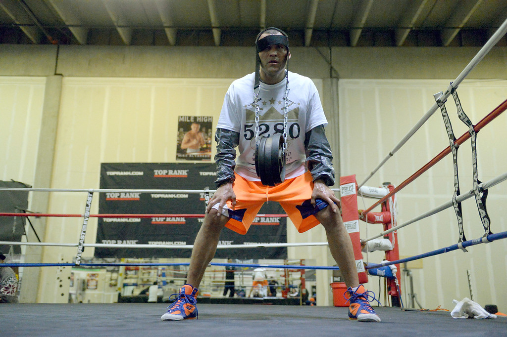 """. DENVER, CO - OCTOBER 15: Colorado\'s only reigning Champion \""""Mile High\"""" Mike Alvarado works on his neck with 35lb weights strapped on his head during a media workout day at Delgado\'s Gym October 15, 2013 as he gets ready for his fight with the Ruslan Provodnikov at 1st Bank Center. (Photo by John Leyba/The Denver Post)"""