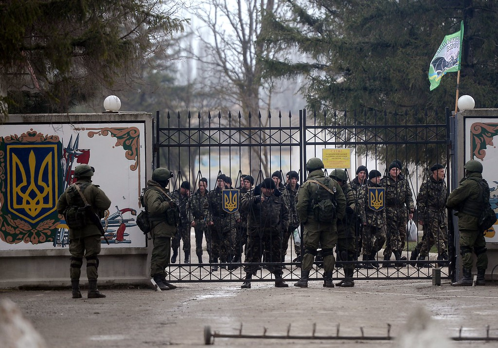 . Russian and Ukranian soldiers talk at the gate of a Ukrainian military unit in the village of Perevalnoye, outside Simferopol on March 20, 2014. AFP PHOTO/ Filippo MONTEFORTE/AFP/Getty Images