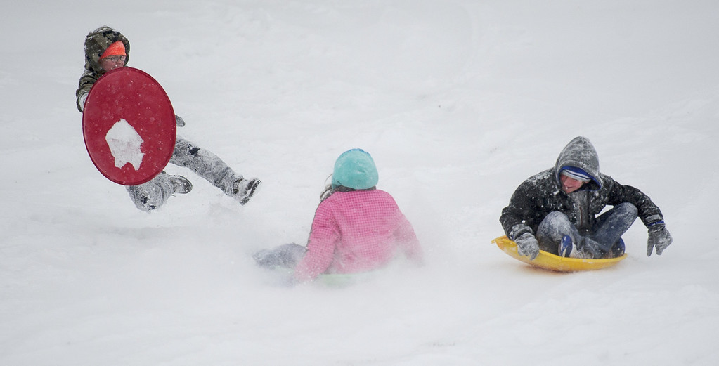 . Ryan Wainwright, 7, leaps out of the way as Jaidyn Richardson, 9, and Kylan France, 11, sled down a hill at Helfrich Hills Golf Course in Evansville, Ind. on Friday, Dec. 6, 2013.   (AP Photo/The Evansville Courier & Press, Brien Vincent)